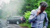 after fire : Mature man making a phone call after a car accident, smoke in the background. Stock Footage