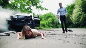 bota : A man running towards a young woman lying on the road after a car accident.