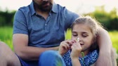 konsantre : A close-up of small girl with her father picking petals off a flower in spring nature.