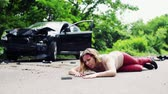 motor : Young injured woman lying on the road after a car accident, trying to reach a phone.