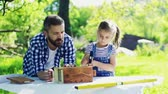 nehty : Father with a small daughter outside, making wooden birdhouse. Dostupné videozáznamy
