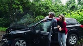 получать : A young woman helping a man to get out of the crashed car after an accident.