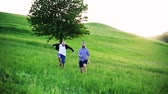 quality time : An adult hipster son with senior father running and jumping in nature.
