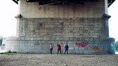 grafiti : Young athlete friends stretching under the bridge in the city.