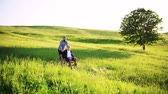 gastos : An adult hipster son with senior father in wheelchair on a walk in nature at sunset. Stock Footage