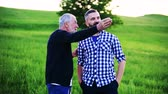 quality time : An adult hipster son with senior father standing in nature, talking.