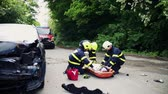 plástico : Firefighters helping a young injured woman after a car accident.