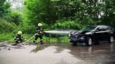 after fire : Two firefighters extinguishing a burning car after an accident. Stock Footage
