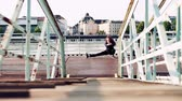 outdoor pursuit : Beautiful young woman stretching on the bridge in the city. Stock Footage