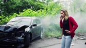 cardigã : Young woman making a phone call after a car accident, smoke in the background. Vídeos