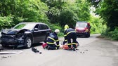 ferido : Firefighters rescuing a young injured woman lying on the road after an accident. Vídeos