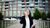 halsband : A young businesswoman with glasses walking on the bridge in a city. Stock Footage