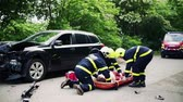 plástico : Firefighters putting an injured woman into a plastic stretcher after a car accident.