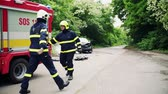 hadice : Two firefighters getting ready to extinguish a burning car after an accident. Dostupné videozáznamy