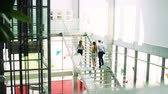 prýmky : A group of businesspeople walking up the stairs in the modern building, talking.