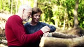 outdoor pursuit : Senior sporty couple standing in the forest outdoors in nature, using smartwatch.