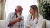 retirement home : Health visitor with stethoscope and a senior man at home, talking.