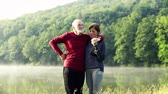 mgła : Senior couple standing by the lake outdoor in foggy morning in nature.