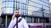 gravata : A hipster businessman with smartphone in the city, making a phone call.