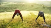 supporting : Senior couple runners stretching on meadow outdoors at sunrise in nature. Stock Footage
