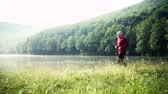 sportbekleidung : Senior man running by the lake outdoor in the morning in nature.