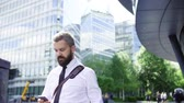 collar : Hipster businessman walking on the street in city, using smartphone.