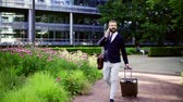 bílý límec : Hipster businessman with smartphone and suitcase walking in park in London.
