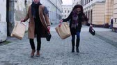 bota : Cheerful teenager couple with paper bags running down the street in winter. Stock Footage