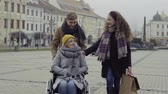 manteau hiver : Teenagers and senior grandmother in wheelchair walking down the street in winter. Vidéos Libres De Droits