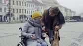 vnuk : A teenager boy with disabled grandmother in wheelchair outdoors on the street in winter.