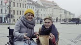 Словакия : A teenager boy with disabled grandmother in wheelchair outdoors on the street in winter.