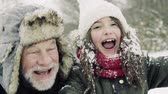 omini : A close-up of grandfather and small girl in snow on a winter day. Filmati Stock
