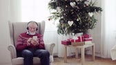 presente de natal : A portrait of senior man with headphones sitting on armchair at home at Christmas time.