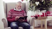 jezus : A senior man reading bible at home at Christmas time.