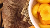 абрикос : Apricots (Canned) rotating on a wooden plate as seamless loopable 4K UHD footage