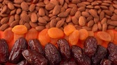 даты : Dried fruits and nuts background, almonds, dates, dried apricots close up from the above