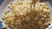 Pouring Frozen Sweet Corn From Bag on a Plate. Close Up 4 K Video of Frozen Corn