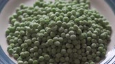 Pouring Frozen Green Peas From Bag on a plate. Close Up 4 K Video of Frozen Peas