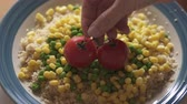 sêmola : Cooked Couscous With Green Peas, Sweet Corn, and Red Tomatoes on a Plate. 4 K Video, Close Up Plate of Couscous with Some Vegetable