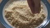 sêmola : Cooked Couscous, Woman Hand. Adding Some Seasoning Salt. Slow Motion, Close Up Plate of Couscous with Seasoning Salt Vídeos