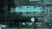 Trains and people at Berlin main station (Berlin Hauptbahnhof) behind glass facade