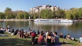 多民族の : Young people sitting on meadow in park at riverside on sunny day in Berlin