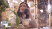 conversation : Young brunette woman viewed through window of cafe talking on the phone, smiling and drinking cacao in cafe Stock Footage