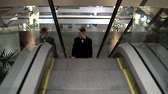 executive : Young man in a black suit with bow tie coming up on the escalator in a shopping mall