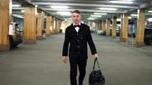 executive : Young gangster in a black suit with bow-tie walking on the parking with big leather bag. Slowmotion Stock Footage