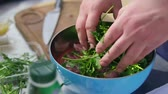 herb : Man is mixing meat pieces with spices and herbs in metal bowl. The wooden surface outside. Barbeque time. Shot in 4k