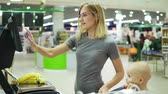 weigher : Young mother weighing bananas using self-service electronic scales in the supermarket while her cute child is sitting in a shopping cart and waiting for the banana