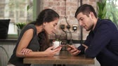 coffee cherries : Attractive young couple in cafe using their phones sitting at the wooden table and drinking milkshake using straws. Happy couple during holidays relaxing in cafe Stock Footage