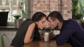 coffee cherries : Attractive young couple in cafe sitting at the wooden table and sharing milkshake drinking it together using two straws. Happy couple during holidays relaxing in cafe Stock Footage