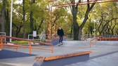 construir : Slowmotion shot of a hipster skateboarder jumping on the pipe in the skatepark. Tries not to fall in the end